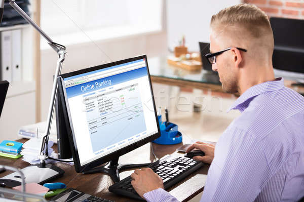 Businessman Doing Online Banking In Office Stock photo © AndreyPopov