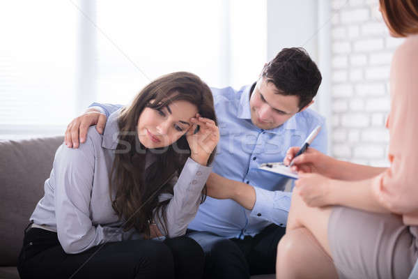 Stock photo: Man Consoling His Wife Sitting With Psychologist