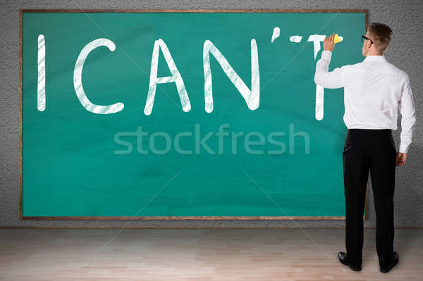 Businessman Rubbing Letter T From I Can't Written On Chalkboard Stock photo © AndreyPopov
