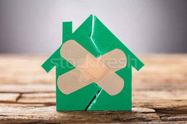 Closeup Of Broken House With Crossed Band Aid Stock photo © AndreyPopov