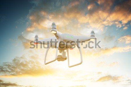 Drone flying against cloudy sky during sunset Stock photo © AndreyPopov