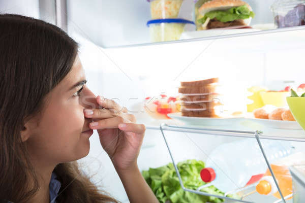 Woman Holding Her Nose Near Foul Food In Refrigerator Stock photo © AndreyPopov