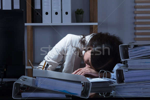 Businesswoman Leaning Head On Desk While Working Late Stock photo © AndreyPopov