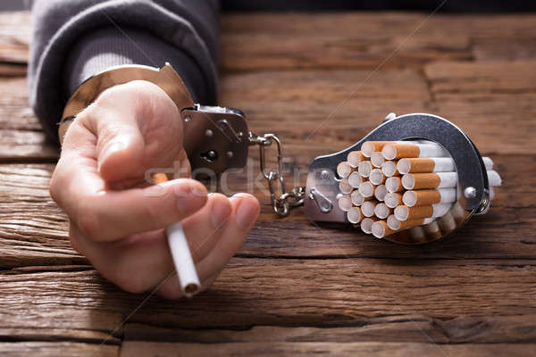 Person's Hand With Handcuffs And Cigarettes Stock photo © AndreyPopov