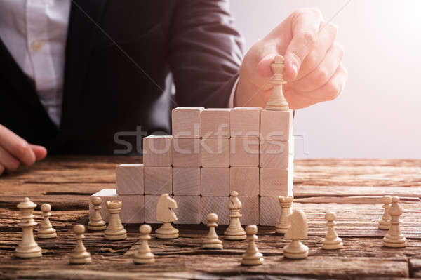 Businessperson Arranging Chess Piece On Wooden Blocks Stock photo © AndreyPopov