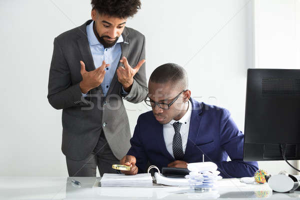 Man With Fingers Crossed Looking At Auditor Analyzing Bill Stock photo © AndreyPopov