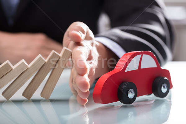 Businessperson's Hand Stopping Wooden Blocks From Falling On Car Stock photo © AndreyPopov
