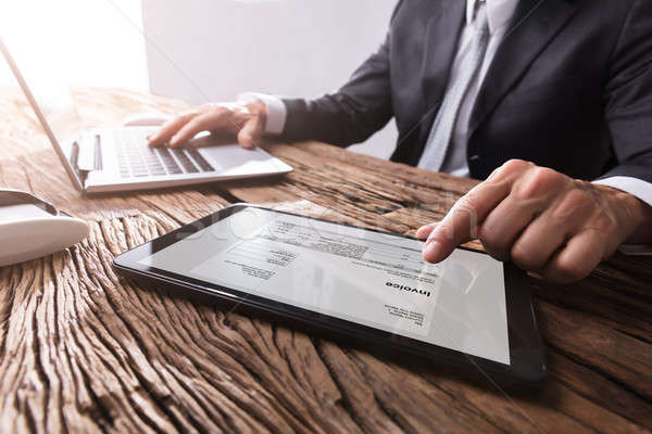 Businessman Working With Invoice On Digital Tablet Stock photo © AndreyPopov