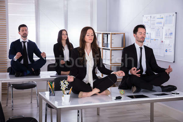 Businesspeople Meditating In Office Stock photo © AndreyPopov
