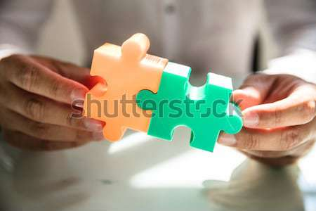 Stock photo: Businessman connecting two jigsaw puzzles