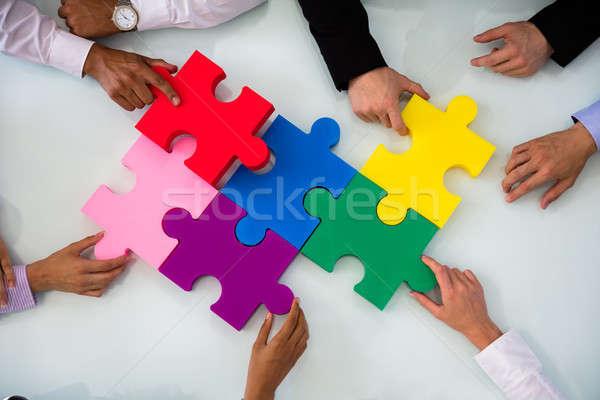 Csoport üzletemberek kirakós játék színes asztal iroda Stock fotó © AndreyPopov