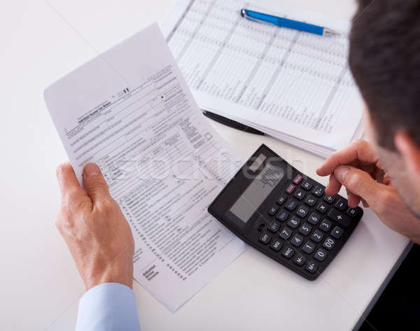 Man checking an invoice on a calculator Stock photo © AndreyPopov