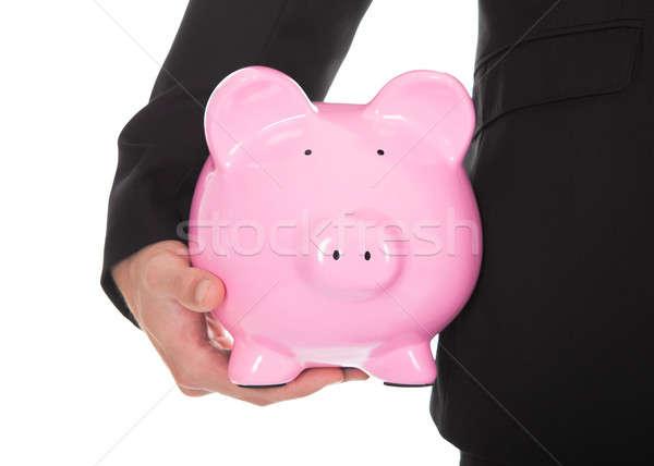 Closeup of businessman holding a pink piggy bank Stock photo © AndreyPopov