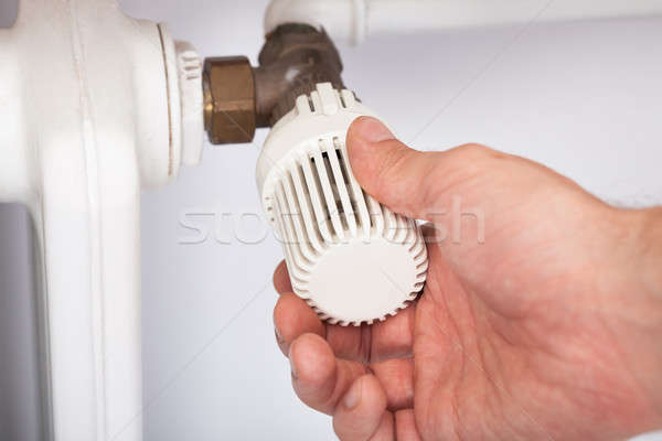 Man Adjusting Temperature On Radiator Thermostat Stock photo © AndreyPopov