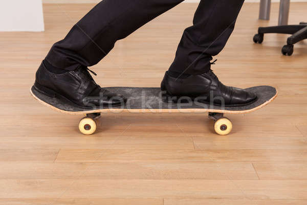 Low section of businessman on skateboard Stock photo © AndreyPopov