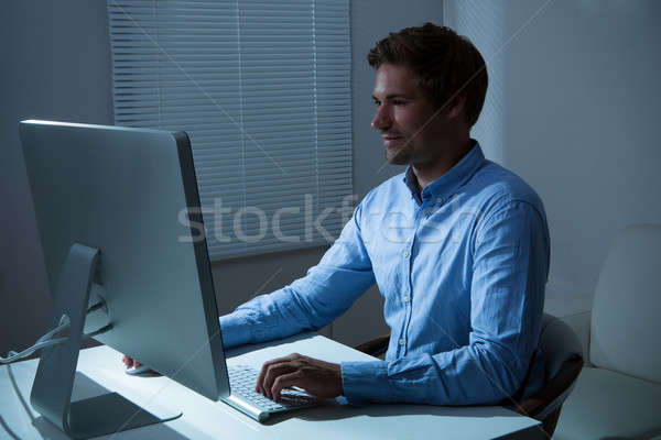 Businessman Working Late At Desk In Office Stock photo © AndreyPopov