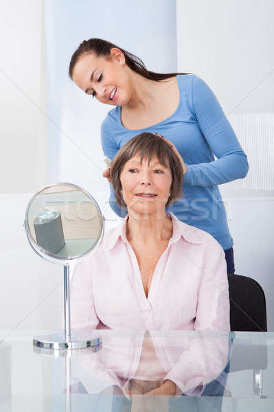 Stock photo: Caretaker Combing Senior Woman's Hair