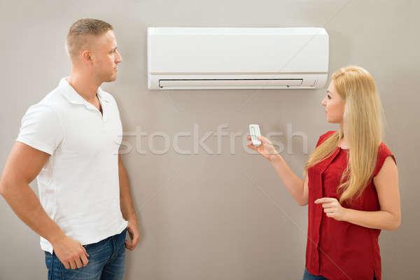 Télécommande climatiseur couple maison homme mur Photo stock © AndreyPopov