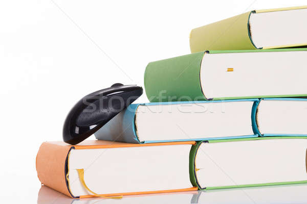 Computer mouse climbing books Stock photo © AndreyPopov