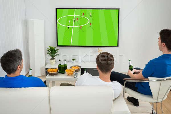 üç erkekler izlerken futbol maç oturma Stok fotoğraf © AndreyPopov