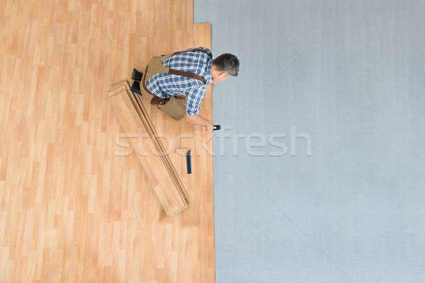 Stock photo: Worker Assembling New Laminate Floor
