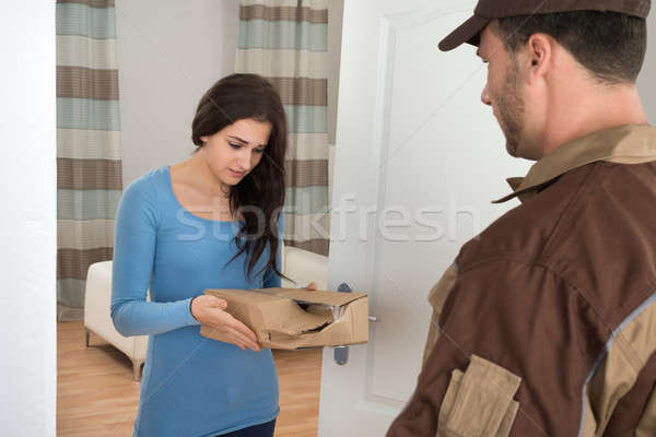 Woman Holding Damaged Package From Delivery Man Stock photo © AndreyPopov