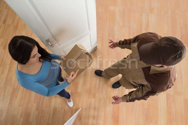 Stock photo: Woman Receiving Damaged Package From Delivery Man