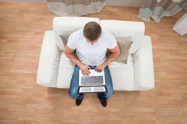 Férfi olvas ekönyv laptop fiatalember kanapé Stock fotó © AndreyPopov
