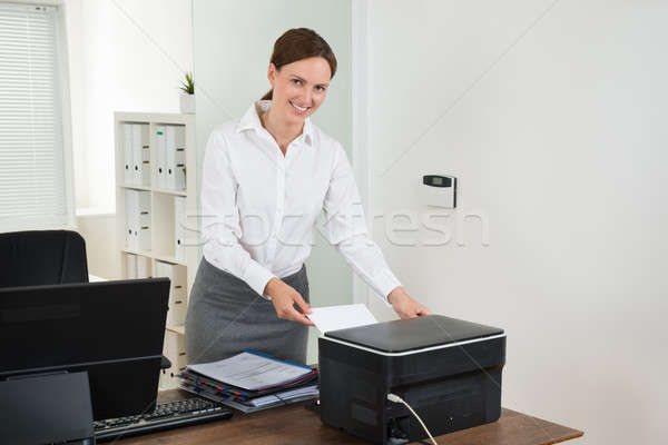 Secretary Inserting Paper In Printer Stock photo © AndreyPopov