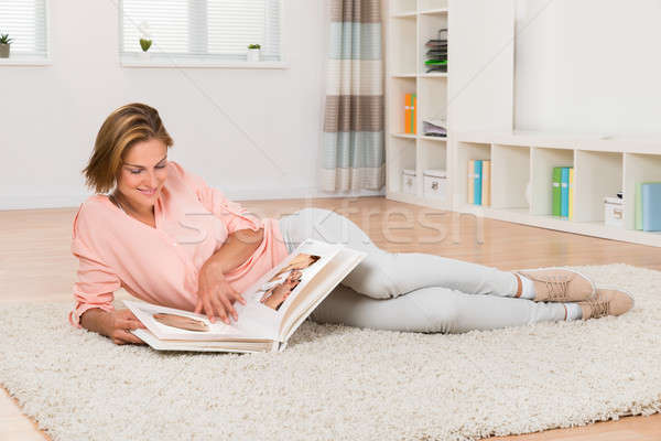 Woman Looking At Photo Album Stock photo © AndreyPopov