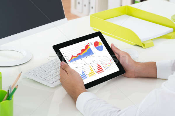 Stock photo: Businessperson Looking At Graphs On Digital Tablet