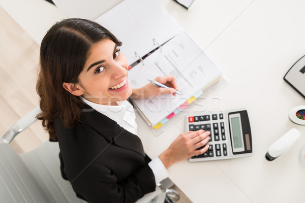 Happy Businesswoman Doing Financial Calculation At Desk Stock photo © AndreyPopov