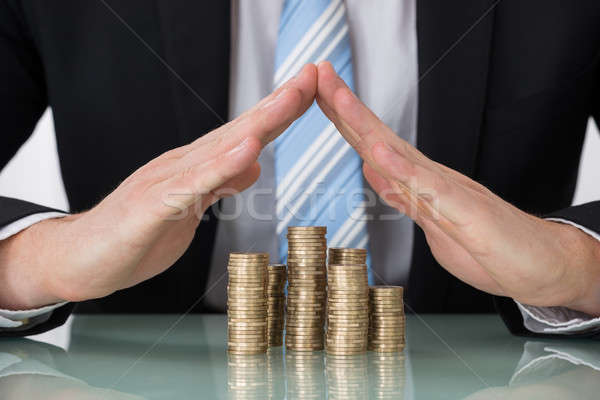 Businessperson Saving Pile Of Coins Stock photo © AndreyPopov