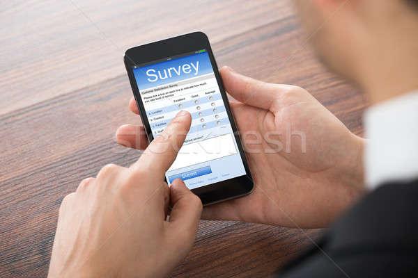 Businessman Filling Online Survey On Mobile Phone Stock photo © AndreyPopov