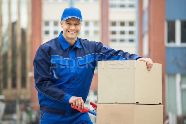 Deliveryman With Trolley Loaded With Cardboard Boxes Stock photo © AndreyPopov