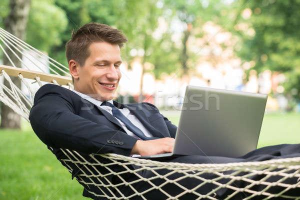 Hombre hamaca usando la computadora portátil feliz joven tecnología Foto stock © AndreyPopov