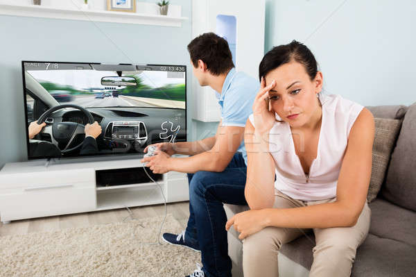 Woman Sitting Beside A Man Addicted To Videogame Stock photo © AndreyPopov
