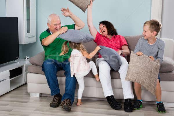 Dziadkowie wnuki pillow fight dzieci posiedzenia kanapie Zdjęcia stock © AndreyPopov