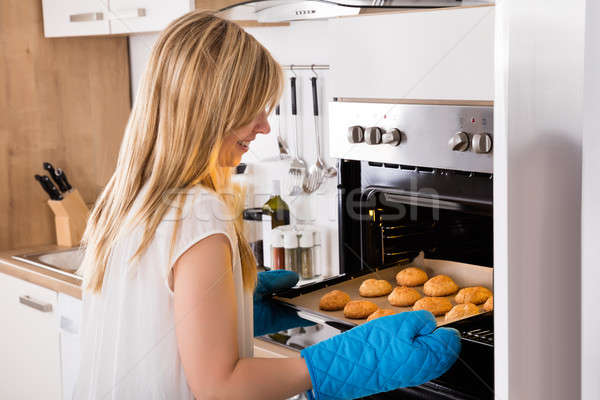 Woman Placing Tray Full Of Cookies In Oven Stock photo © AndreyPopov