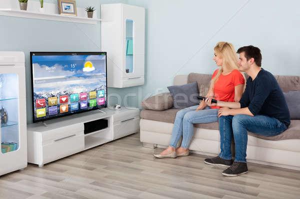 Stock photo: Couple Sitting On Sofa Watching Television