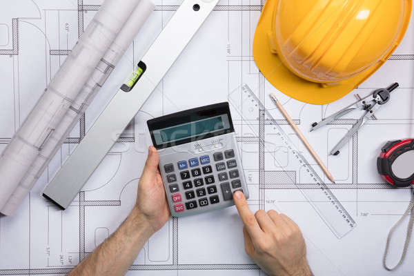 Stock photo: Architect hands using calculator working on blueprint