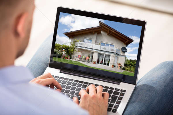 Man Looking At House Exterior On Laptop Stock photo © AndreyPopov