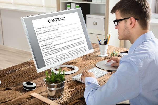 Imprenditore guardando contratto schermo del computer primo piano giovani Foto d'archivio © AndreyPopov
