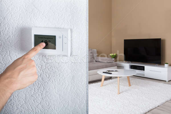 Person's Hand Adjusting Digital Thermostat Stock photo © AndreyPopov