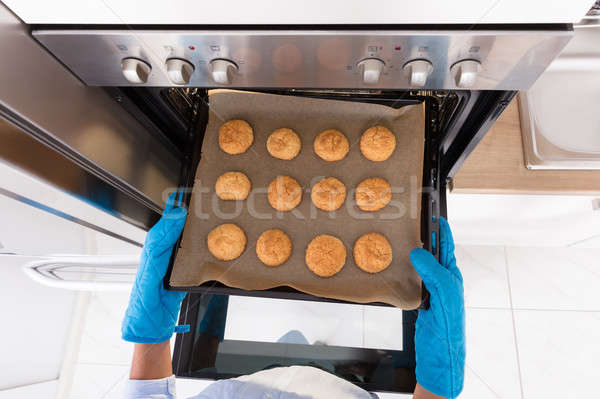 Taking Out Tray Of Baked Cookies From Oven Stock photo © AndreyPopov