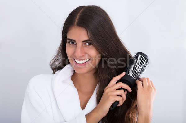Happy Woman In Bathrobe Combing Hair Stock photo © AndreyPopov
