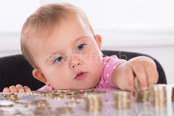 Baby Stacking Coins On Desk Stock photo © AndreyPopov