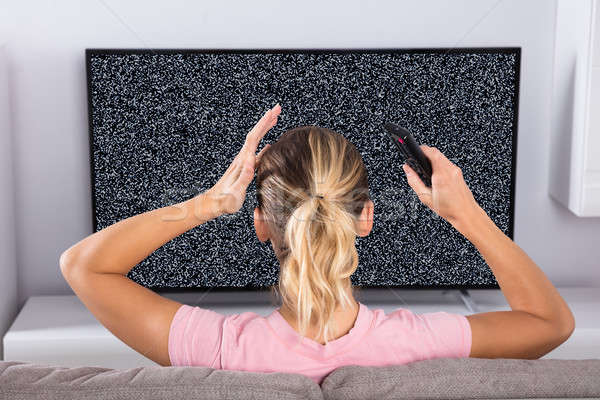 Woman Frustrated With A TV Screen Glitch Stock photo © AndreyPopov