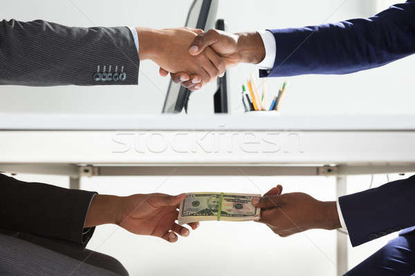 Two Businesspeople Shaking Hand And Taking Bribe Stock photo © AndreyPopov