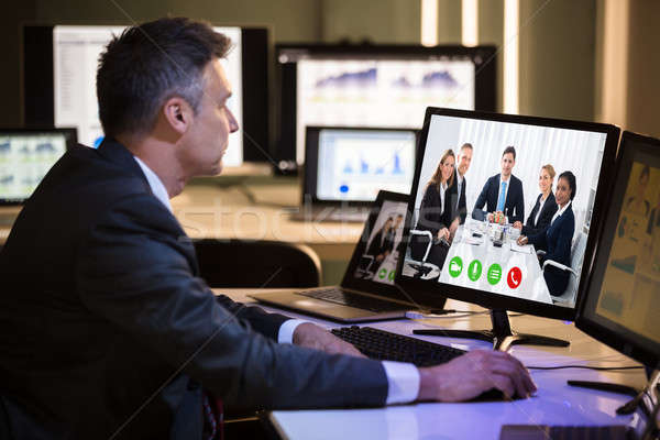 Businessman Video Conferencing With Happy Colleagues On Computer Stock photo © AndreyPopov